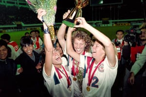Michelle Akers holds the trophy aloft.