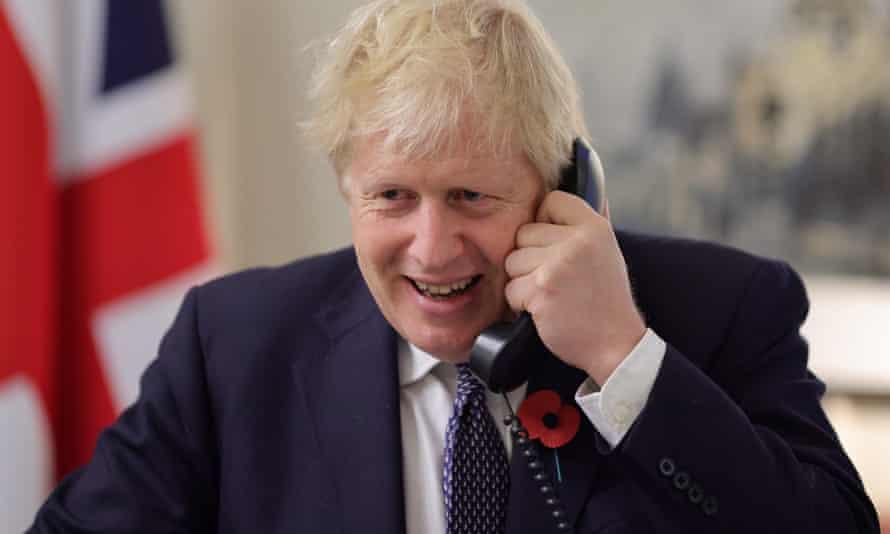Boris Johnson on phone with UK flag behind him