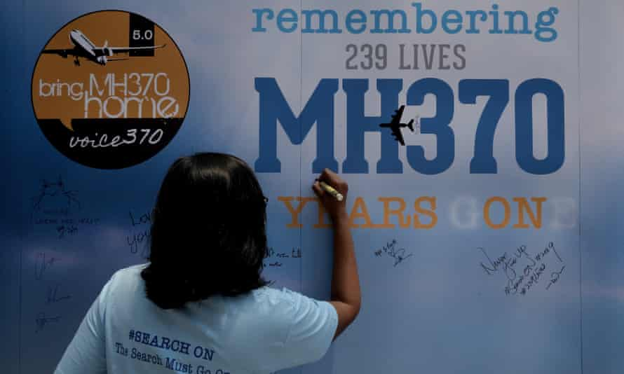 A family member writes on a message board during the five-year memorial event for the missing Malaysia Airlines flight MH370 in Kuala Lumpur.