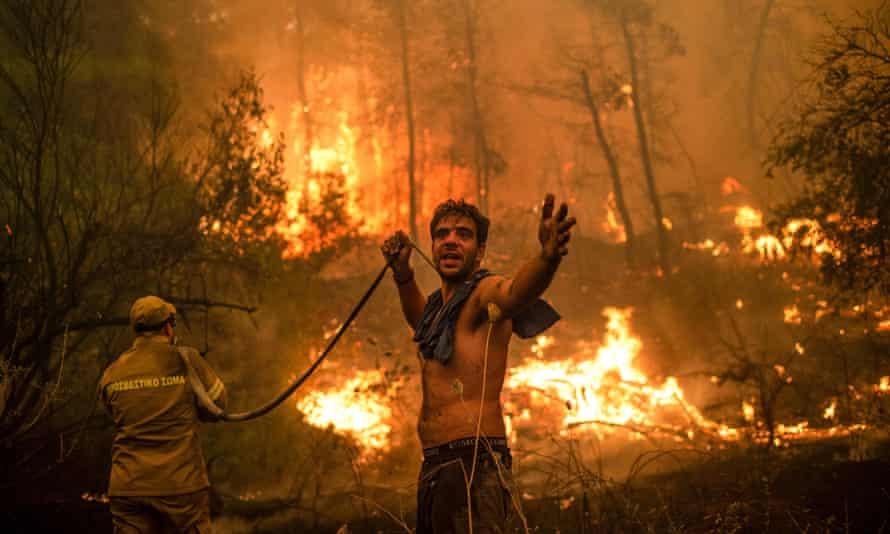 Uma mangueira de água está vazia para um voluntário que luta contra incêndios florestais perto do vilarejo de Pefki, na ilha grega de Evia.