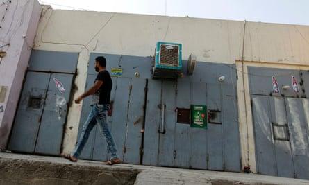 An Iraqi man walks past a closed liquor store in the capital Baghdad.