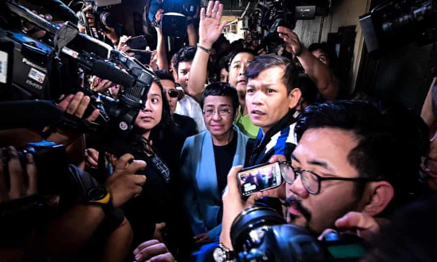 Philippine journalist Maria Ressa (in a blue jacket), surrounded by press and TV journalists