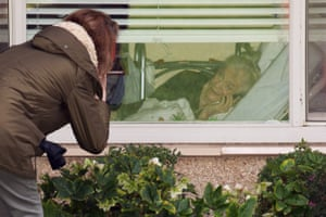 Lori Spencer talks on the phone through a window with her mother, Judie Shape, 81, who was tested for coronavirus, at the Life Care Center of Kirkland, the long-term care facility linked to confirmed coronavirus cases in the state, in Kirkland, Washington