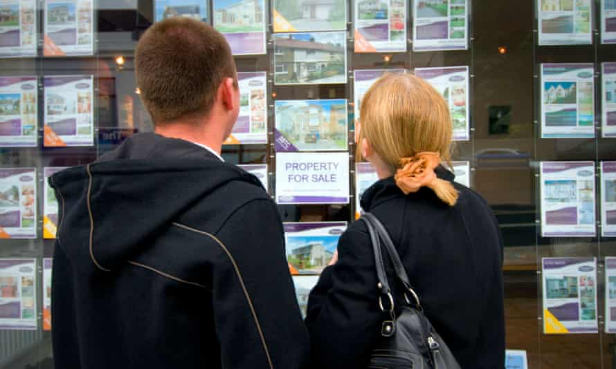 Young couple looking at houses in estate agent's window