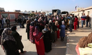 Refugees line up to receive humanitarian aid in Syria.