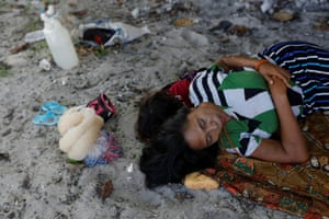 Woman and child rest on sand