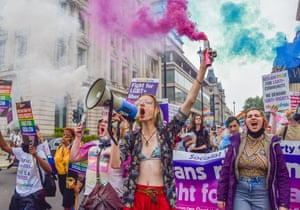 A demonstrator shouts through a megaphone and holds a smoke flare in Pall Mall during the Reclaim Pride protest