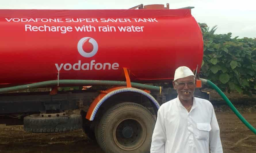 A farmer stands beside one of Vodafone's water tankers