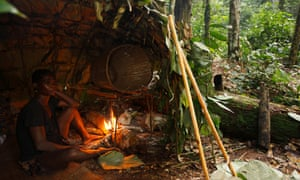 Baka man taking shelter in a Mongolu at a forest hunting camp, Cameroon.