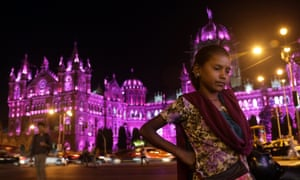 International Women's Day in Mumbaiepa05834729 An Indian girl stands in front of the Chhatrapati Shivaji Maharaj Terminus (CSMT) railway station, lit up in pink colour on the eve of International Women's Day, in Mumbai, India, 07 February 2017. International Women's Day is celebrated globally on 08 March to promote women's rights and equality. EPA/DIVYAKANT SOLANKI