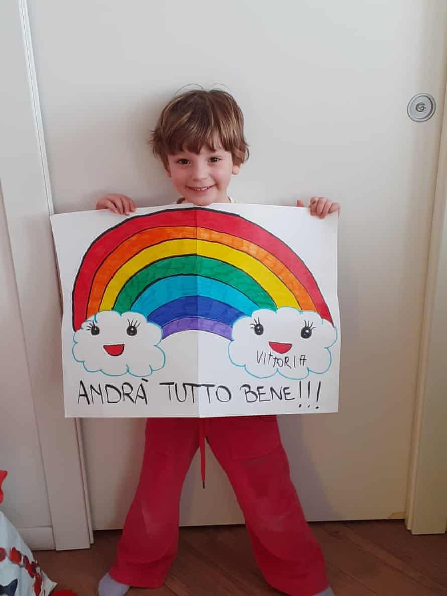 A child holding up an encouraging rainbow drawing.