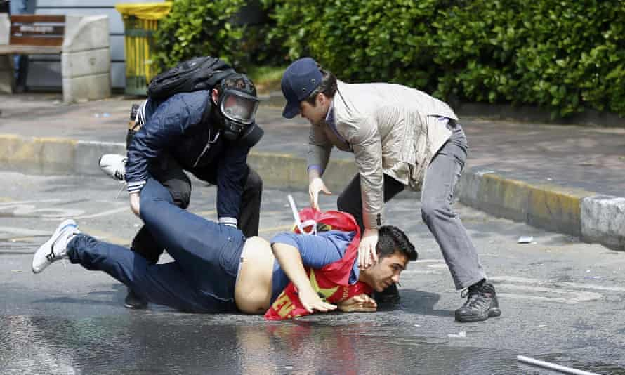 Plainclothes policemen detain a protester during clashes in Besiktas neighbourhood of Istanbul