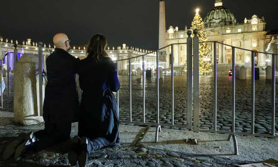 People pray outside St Peter's square during the Christmas Eve mass celebrated by Pope Francis in Italy.