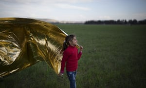 A young girl plays with a survival blanket in the wind on the Greek-Macedonia border at Idomeni.