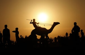 Rafah, Gaza: The silhouette of a jockey competing in a camel race at the destroyed airport