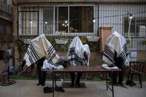 Ultra-Orthodox Jews pray covered in prayer shawls next to their house after synagogues were closed following government measures to help stop the spread of the coronavirus.