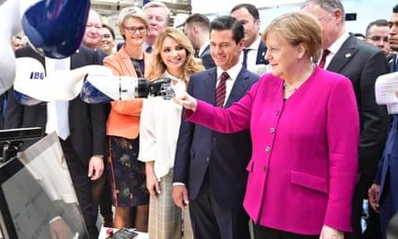 German Chancellor Angela Merkel greets a robot at the Hanover Fair in April.