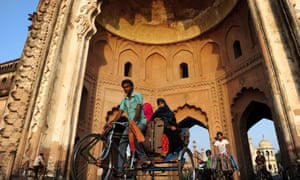 A rickshaw driver transports passengers past the Rumi Darwaza gateway in Lucknow, where a microcredit programme helps drivers to buy their own rickshaws.