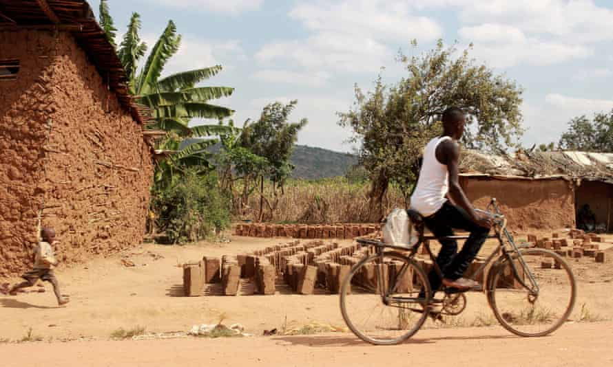 A boy cycles past rows of bricks in Nakivale while a child runs alongside