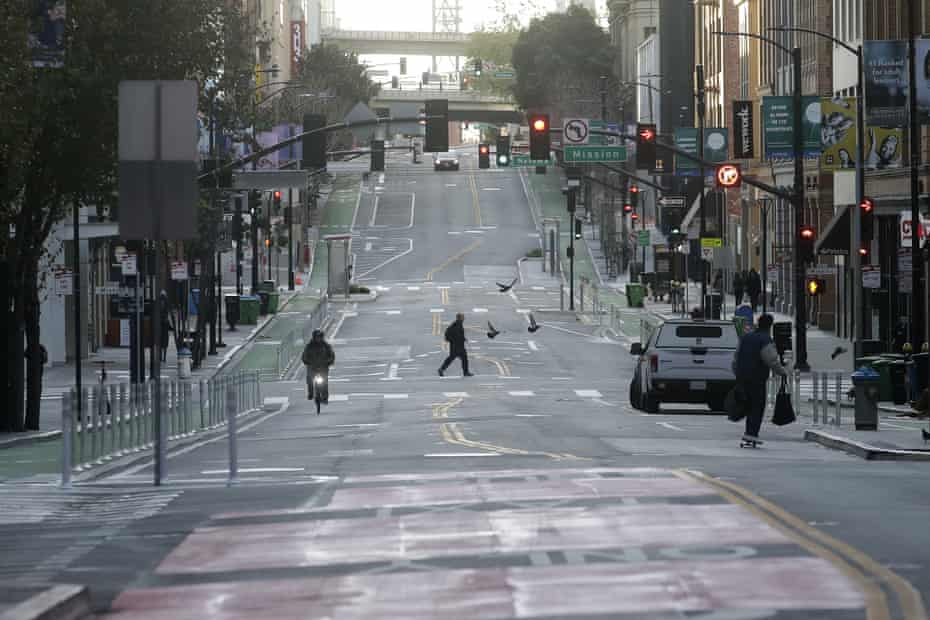 A man crosses a nearly empty street in San Francisco on Tuesday.