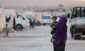 A displaced Syrian woman holds a toddler in a camp in Kafaldin. The US will reduce the number of refugees entering by a third.