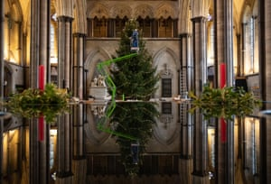 Salisbury, England. Ecclesiastical joiner Richard Pike places decorations on the 32ft Norway spruce Christmas tree as it is decorated inside Salisbury Cathedral. This is his 30th year working on the cathedral's Christmas tree