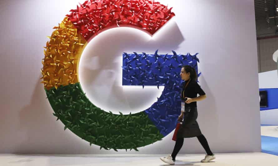 A woman carries a fire extinguisher past the logo for Google at the China International Import Expo in Shanghai earlier this month.