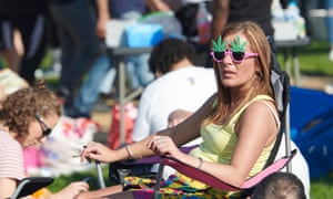 Woman sitting and smoking wearing cannabis-leaf sunglasses