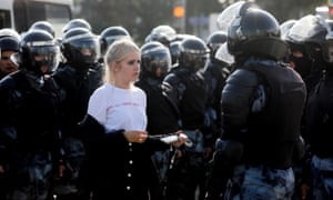 A woman is held by riot police at a rally in Pushkinskaya Square in Moscow on 3 August.