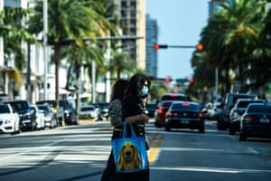 A woman wears a mask as she walks in Miami Beach, Florida on Thursday.