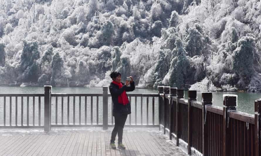 A woman photographs the scene at Hangzhou, in eastern China's Zhejiang province.