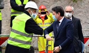 The Italian prime minister, Giuseppe Conte (R), greets Genoa's mayor, Marco Bucci
