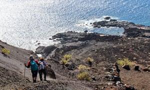 Women walking the lava fields and coast of El Hierro, Canary Islands, Spain.
