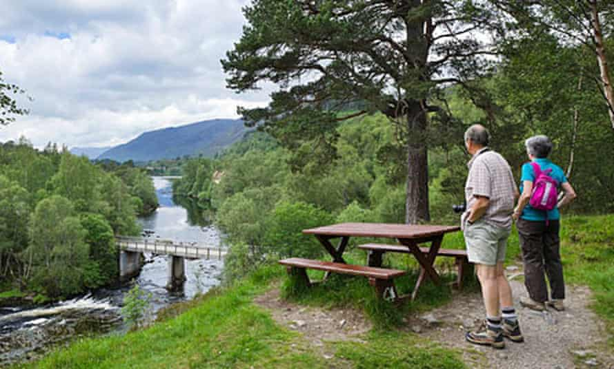 Walkers admiring the view over the River Affric looking towardds Loch Affric, Glen Affric, in Scotland.