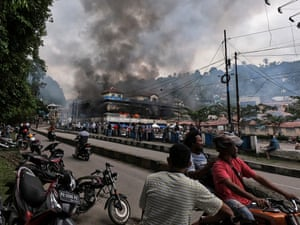 Papuans gather while the Buruni market burns after protesters, Wednesday, Aug. 21, 2019.