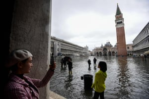 Tourists take photographs of the flooded St Mark's Square in Venice.