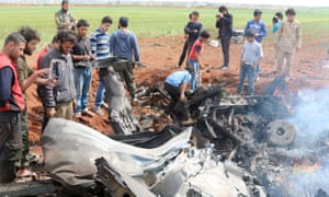 Rebel fighters and civilians gather around the wreckage of a Syrian warplane that was shot down south of Aleppo.