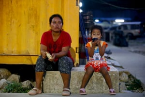 A young girl uses a mobile phone next to her mother