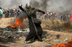 A girl hurls stones during clashes with Israeli troops at the border between Israel and Gaza.