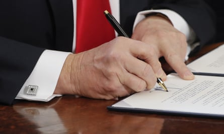Donald Trump signs an executive order in the Oval office of the White House.