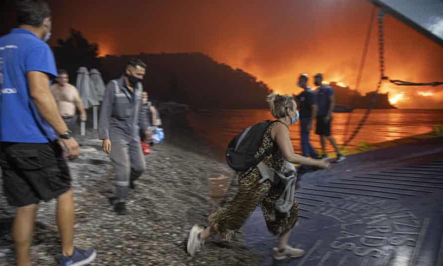 People boarding a ferry in Evia as flames burn in the background
