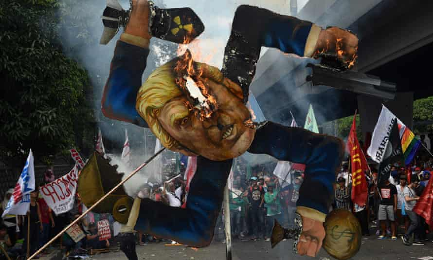 Protesters burn an effigy of Donald Trump at a march in Manila.