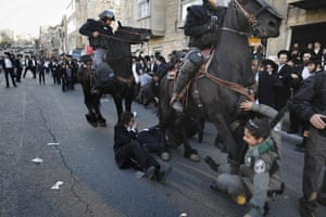 Israeli mounted policemen run into a policewoman as they attempt to disperse ultra-Orthodox Jews during a protest against Israeli army conscription in Jerusalem.