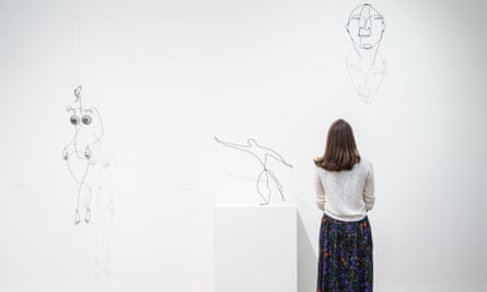 A woman admires some of Alexander Calder's mobile sculptures at a preview of Tate Modern's Performing Sculpture show.