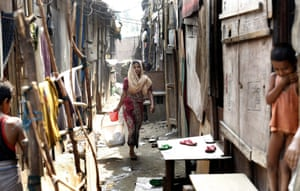 A Rohingya refugee woman returning home after washing her clothes in a makeshift settlement in Madanpur Khadar on the eve of World Refugee Day