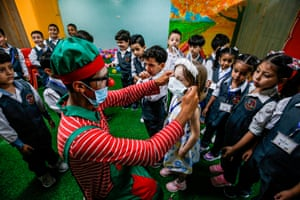 A clown instructs children how to wear a face mask during a Covid-19 awareness session at a kindergarten in Gaza City.