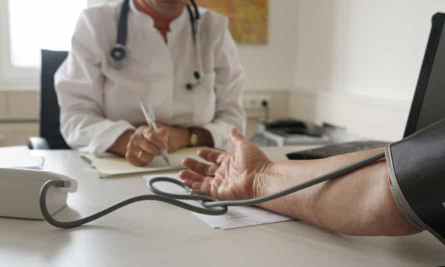 A doctors tests blood pressure