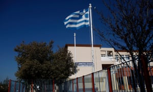 A Greek flag flutters behind the entrance of a closed school in Kalyvia suburb south of Athens, 11 March 2020. Greek government on 10 March announced that all schools in the country will remain closed for the next two weeks, in an attempt to stop the wild spread of coronavirus.