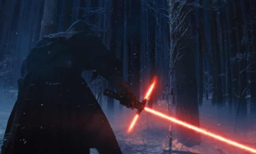 Kylo Ren with his lightsaber in a scene from Star Wars: The Force Awakens.