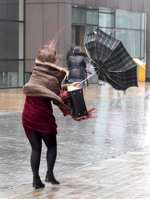 A woman struggles with an umbrella in Manchester